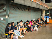 """03 JANUARY 2017 - BANGKOK, THAILAND: Passengers wait to board their bus at Ekkamai Bus Terminal in Bangkok Tuesday. Travelers flocked to Bangkok's bus and train stations Tuesday, the last day of the long New Year's weekend in Thailand. The New Year holiday in Thailand is called the """"seven deadly days"""" because of the number of fatal highway and traffic accidents. As of Monday Jan 2, 367 people died in highway accidents over the New Year holiday in Thailand, a 25.7% increase over the same period in 2016.        PHOTO BY JACK KURTZ"""