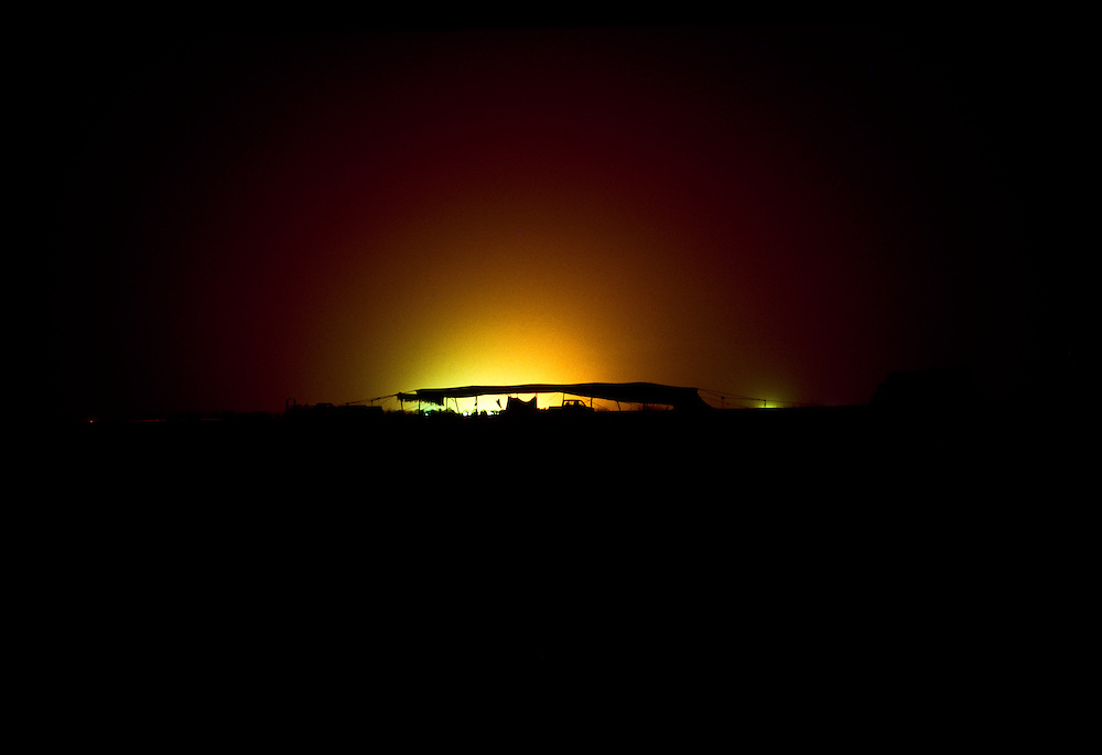 Light from oil rig flare backlights a Bedouin tent in southern Arabia.