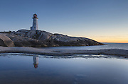 Peggy's Cove Lighthouse reflected in pool of water on granite shoreline, Nova Scotia