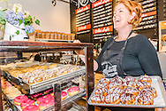Maria Moore Riggs, owner of Revolution Doughnuts & Coffee, holds a tray of Nutella cream puffs as she greets customers, June 12, 2014, in Decatur, Georgia. The family-owned business opened in 2012. (Photo by Carmen K. Sisson/Cloudybright)