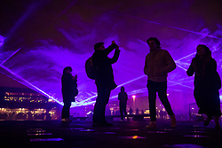 **2018 Pictures of the year by London News Pictures**<br /> © Licensed to London News Pictures. 17/01/2018. London, UK. Visitors walk through a laser and smoke light show entitled 'Waterlicht' by Daan Roosegaarde as it fills the night sky above Granary Square in King's Cross during the Lumiere London festival. Running from 18th-21st January 2018 more than 50 artworks? are transforming the capital's streets, buildings and public spaces into an immersive nocturnal art exhibition of light and sound. Locations include King's Cross, Fitzrovia, Mayfair, West End, Trafalgar Square, Westminster, Victoria, South Bank and Waterloo. Photo credit: Peter Macdiarmid/LNP