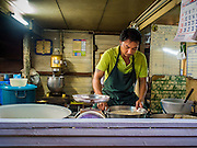 "22 DECEMBER 2014 - BANGKOK, THAILAND: A worker at Thanusingha Bakery mixes batter for traditional Thai Catholic desert cakes. The cakes are called ""Kanom Farang Kudeejeen"" or ""Chinese Monk Candy."" The tradition of baking the cakes, about the size of a cupcake or muffin, started in Siam (now Thailand) in the 17th century AD when Portuguese Catholic priests accompanied Portuguese soldiers who assisted the Siamese in their wars with Burma. Several hundred Siamese (Thai) Buddhists converted to Catholicism and started baking the cakes. When the Siamese Empire in Ayutthaya was sacked by the Burmese the Portuguese and Thai Catholics fled to Thonburi, in what is now Bangkok. The Portuguese established a Catholic church near the new Siamese capital. Now just three families bake the cakes, using a recipe that is 400 years old and contains eggs, wheat flour, sugar, water and raisins. The same family has been baking the cakes at the Thanusingha Bakery, near Santa Cruz Church, for more than five generations. There are still a large number of Thai Catholics living in the neighborhood around the church.     PHOTO BY JACK KURTZ"