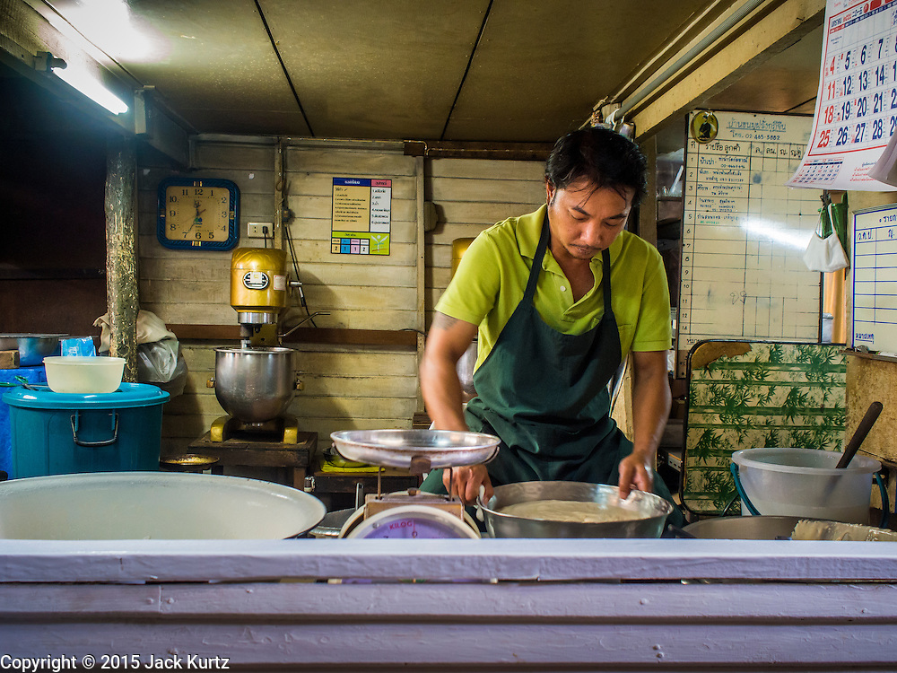 """22 DECEMBER 2014 - BANGKOK, THAILAND: A worker at Thanusingha Bakery mixes batter for traditional Thai Catholic desert cakes. The cakes are called """"Kanom Farang Kudeejeen"""" or """"Chinese Monk Candy."""" The tradition of baking the cakes, about the size of a cupcake or muffin, started in Siam (now Thailand) in the 17th century AD when Portuguese Catholic priests accompanied Portuguese soldiers who assisted the Siamese in their wars with Burma. Several hundred Siamese (Thai) Buddhists converted to Catholicism and started baking the cakes. When the Siamese Empire in Ayutthaya was sacked by the Burmese the Portuguese and Thai Catholics fled to Thonburi, in what is now Bangkok. The Portuguese established a Catholic church near the new Siamese capital. Now just three families bake the cakes, using a recipe that is 400 years old and contains eggs, wheat flour, sugar, water and raisins. The same family has been baking the cakes at the Thanusingha Bakery, near Santa Cruz Church, for more than five generations. There are still a large number of Thai Catholics living in the neighborhood around the church.     PHOTO BY JACK KURTZ"""