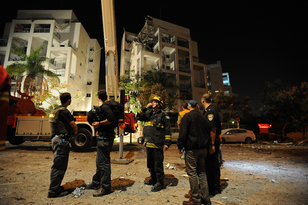 Rishon Letzion, Israel - November 20, 2012:  Rescue forces are seen near a building in Rishon Letzion, located near Tel Aviv, is seen after it was directly hit by a rocket, fired from Gaza Strip, causing the light injury of two cevilians, at the Seventh day of Operation Pillar of Defense. Photo by Gili Yaari  - Israel Photojournalist