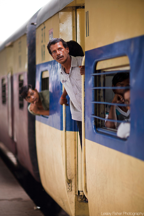 Passengers hanging on to a departing train at New Delhi Train Station, Delhi, India