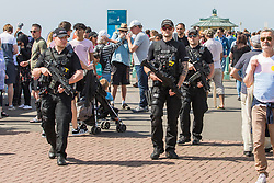 © Licensed to London News Pictures. 22/04/2018. Brighton, UK. Armed police officers patrol the Brighton and Hove promenade. Members of the public take to the beach in Brighton and Hove as warm and sunny weather continues to hit the South-east. Photo credit: Hugo Michiels/LNP