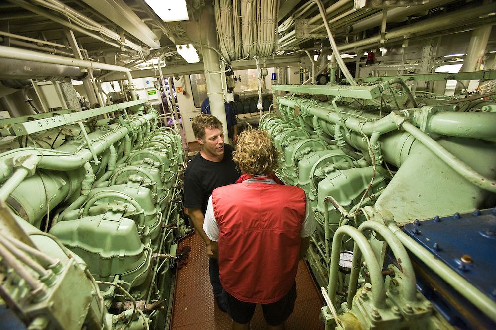 "Two engineers talkin the engine room of Battleaxe, an ocean going tug. Battleaxe was in Horta for a  salvage assignment. The main town of Horta on the Portuguese island of Faial. Faial is one of nine islands in the Azores group which lies 800 miles from the coast of Portugal and marks the most westerly boundary of the European Union. .The engine room of the ocean going tug ""Battleaxe"" Battleaxe was in the azores to assist with the salvage of the cargo ship ""Valor"" which beached itself on the islands northern shore in January 2006. The Portuguese island of Faial. Faial is a stop on the annual transatlantic migration of yachts from the Caribbean to Europe.  Faial is one of nine islands in the Azores group which lies 800 miles from the coast of Portugal and marks the most westerly boundary of the European Union."