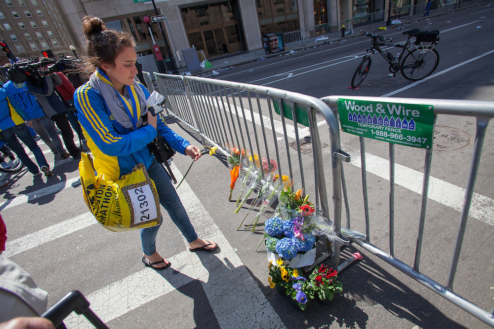 Boston College Senior and marathon runner Marissa Irwin lays a flower against a police barricade near the site of deadly twin bombings at the marathon, in Boston, Massachusetts, USA on 16 April 2013. Irwin finished the marathon less than two minutes before the blasts. At least three people died and more than a hundred were injured in an apparent terrorist attack in the northeastern US city.