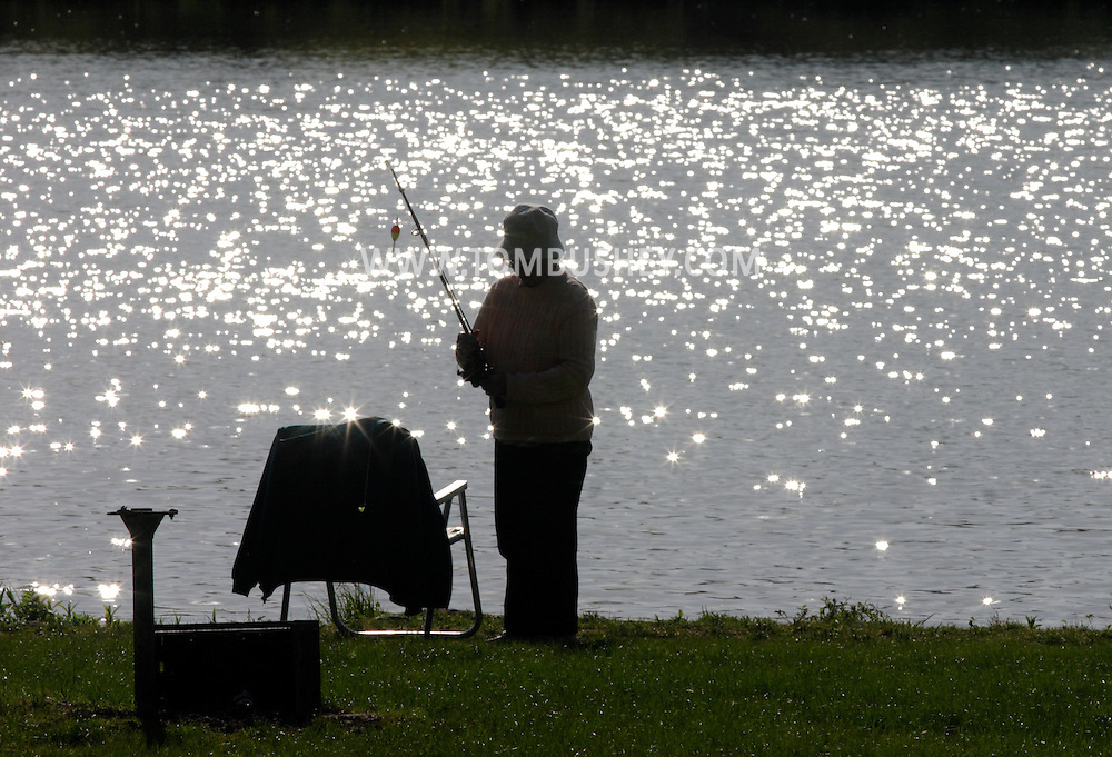 Middletown, N.Y. - A woman starts to put away her rod and reel after fishing in the lake at Fancher-Davidge Park on May 4, 2006. ©Tom Bushey
