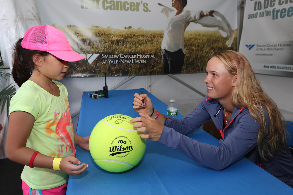 August 16, 2014, New Haven, CT:<br /> Caroline Wozniacki signs an autograph in the Yale New Haven Health booth during WTA All-Access Hour on day three of the 2014 Connecticut Open at the Yale University Tennis Center in New Haven, Connecticut Sunday, August 17, 2014.<br /> (Photo by Billie Weiss/Connecticut Open)