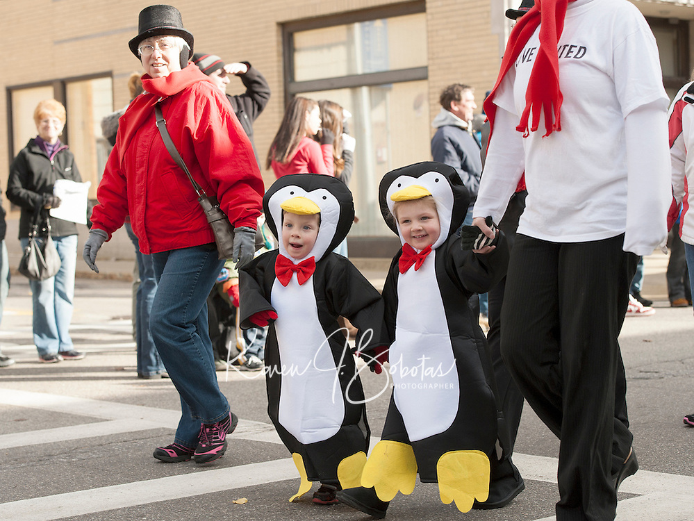 Two happy penguins are among the marchers in Laconia's festive annual Holiday Parade down Main Street Saturday afternoon.  (Karen Bobotas/for the Laconia Daily Sun)