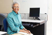 Female teacher holding book in computer classroom, portrait