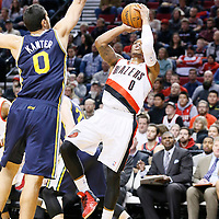 06 December 2013: Portland Trail Blazers point guard Damian Lillard (0) takes a jumpshot over Utah Jazz center Enes Kanter (0) during the Portland Trail Blazers 130-98 victory over the Utah Jazz at the Moda Center, Portland, Oregon, USA.