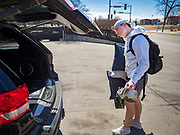 """13 MARCH 2020 - DES MOINES, IOWA: GAGE VANDERLEER, a first year student at Drake University, packs his car before going home for spring break. The Governor of Iowa announced Friday that 17 people in Iowa have tested positive for the Novel Coronavirus. Of those, 15 people were exposed on the same cruise in Egypt, the others were exposed through travel but were not on the same cruise. The Governor said there has not yet been any """"community spread"""" in Iowa. All of the Iowans who have tested positive are in self quarantine. Across Iowa, municipalities and businesses are taking steps to implement """"social distancing."""" Most of the colleges in Iowa, including Drake University, have announced that they will remain closed after their spring breaks and that classes will move to online only, after spring break. Many businesses in Des Moines, including Nationwide Insurance and EMC Insurance, have announced plans to have their employees to telecommute. The mayor of Des Moines has urged event planners to consider canceling large events.     PHOTO BY JACK KURTZ"""