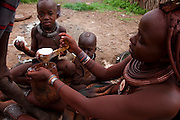 A traditionally dressed Himba woman feeds children outside her home in Okapembambu in northwestern Namibia. The Himba diet consists of corn meal porridge and sour cow's milk. Mopane worms are also a delicacy during the  rainy season.