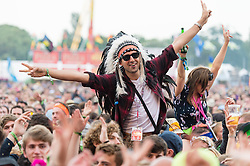 © Licensed to London News Pictures. 12/06/2015. Isle of Wight, UK.  Festival goers dance on their friends shoulders watch Counting Crowes perform on the main stage at Isle of Wight Festival 2015 on Friday Day 2.  Yesterday the weather was hot and Sunny.  Today rain is forecast.  This years festival include headline artists the Prodigy, Blur and Fleetwood Mac.  Photo credit : Richard Isaac/LNP