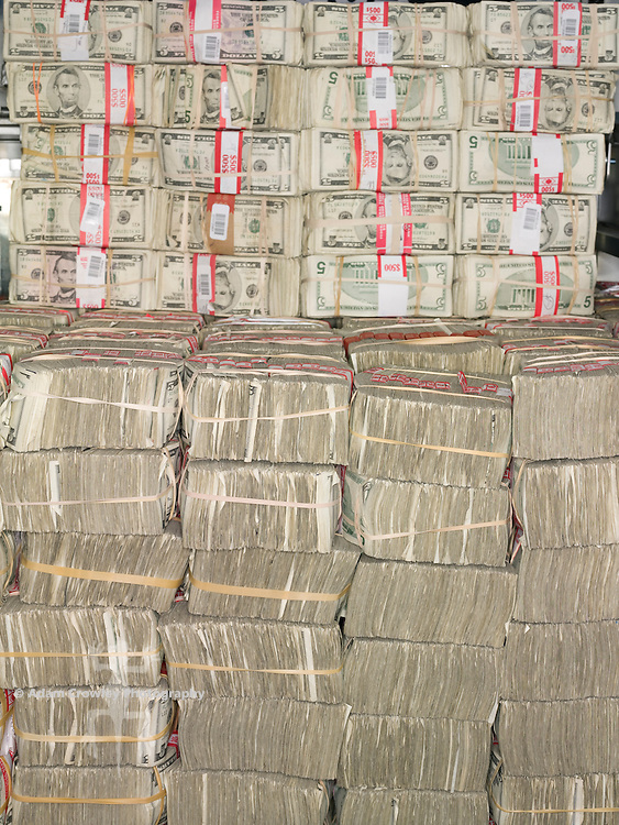 Bundles of U.S. five dollar bills stacked.