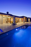 Rear view of luxury villa at night time with swimming pool