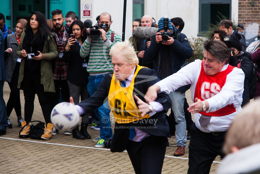 Ealing, London, December 9th 2014. Mayor of London Boris Johnson visits Ealing, Hammersmith and Fulham College accompanied by   Deputy Mayor for Policing and Crime Stephen Greenhlagh to launch a new initiative to increase black and ethnic minority applicants to the Met. PICTURED: Boris Johnson and Stephen Greenhlagh grapple for the ball during a game of netball.