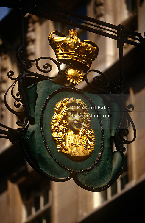 A detail of a City of London Goldsmith's street sign on the corner of Suffolk Lane and Lombard Street in the heart of the capital's financial district. A golden crown sits above the head of an eminent 18th century financier.