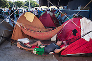 A man sleeps in a hammock in one of the tent areas at the site set up for football fans who had nowhere to stay but the tents, campervans, cars and caravans that they had bought with them. The site, at the Terreirao Do Samba, Rio de Janeiro, Brazil, was arranged by the city government once they realised the number of fans in this situation was significant and rather than having them scattered about the sity they offered secure, enclosed accommodation with sanitation and water. The majority of fans at the site were Argentinian but there were also people from Chile, USA, Uruguay and Colombia. <br /> Picture by Andrew Tobin/Focus Images Ltd +44 7710 761829<br /> 06/07/2014