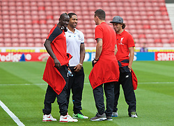 STOKE-ON-TRENT, ENGLAND - Sunday, August 9, 2015: Liverpool's Mamadou Sakho wraps his jacket around former team-mate Stoke City's Glen Johnson as Dejan Lovren and Lazar Markovic look on before the Premier League match at the Britannia Stadium. (Pic by David Rawcliffe/Propaganda)