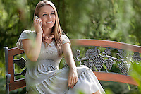 Smiling young woman using mobile phone on park bench