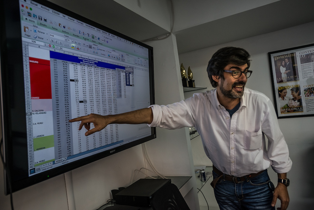 "CARACAS, VENEZUELA - MAY 6, 2015: Comedian Rafael Briceño goes over a chart of inflation rates in Venezuela while working with other members of the Chigüire Bipolar staff to write the script of an upcoming episode of the faux news show, ""Weekly Report"", a comedy sketch led by Briceño and published on www.elchiguirebipolar.net, commonly referred to as Venezuela's version of www.theonion.com.  PHOTO: Meridith Kohut for Buzzfeed News"