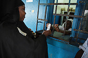 A woman picks up her prescription from the pharmacy counter of the Libreville health center in Man, Cote d'Ivoire on Wednesday July 24, 2013.