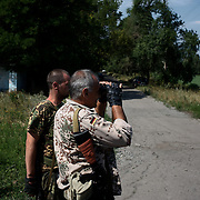 Local rebel fighters monitor movements in the distance where shelling and combate between the Ukrainian army and rebels forces is happening.