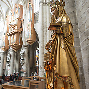 A statue of Saint Gudula (with the pipe organ in the background) at the Cathedral of St. Michael and St. Gudula (in French, Co-Cathédrale collégiale des Ss-Michel et Gudule). A church was founded on this site in the 11th century but the current building dates to the 13th to 15th centuries. The Roman Catholic cathedral is the venue for many state functions such as coronations, royal weddings, and state funerals. It has two patron saints, St Michael and St Gudula, both of whom are also the patron saints of Brussels.