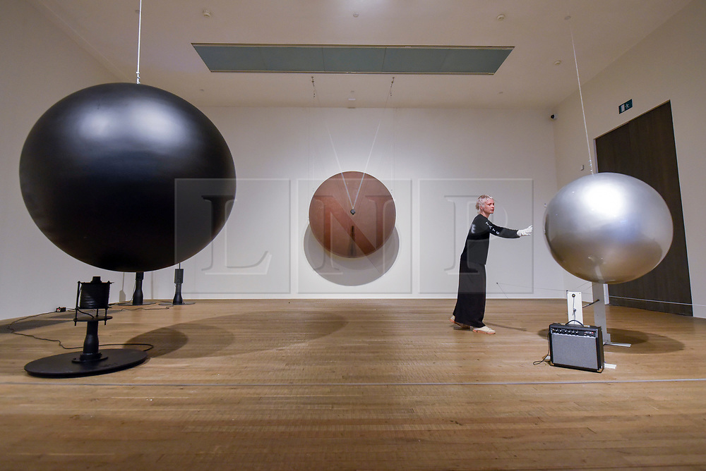 "© Licensed to London News Pictures. 02/07/2019. LONDON, UK.  A staff member with (L to R) ""Electromagnetic Sphere"", 1979, ""Gong"", 1978, and ""Musical Sphere"", 1985, all by Takis. Preview of a new display by the Greek sculptor Takis at Tate Modern.  The retrospective features over 80 works in Takis' largest exhibition in the UK to date and combines works involving magnetism, light and sound.  The show runs 3 July to 27 October.  Photo credit: Stephen Chung/LNP"