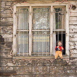 Small Child Sitting in Window of Delapidated Old Residence in Istanbul, Turkey