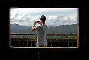 An expedition member takes a picture of the view over Danum Valley. Raleigh International environmental conservation project, Alpha 4, Danum Valley, Sabah, Malaysian, Spring 2008.