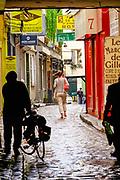 France, Paris, Man walking down  Passage du Chantier in a trench coat.