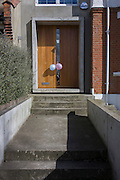 Two birthday party balloons on the front door of a modern house in southy London.