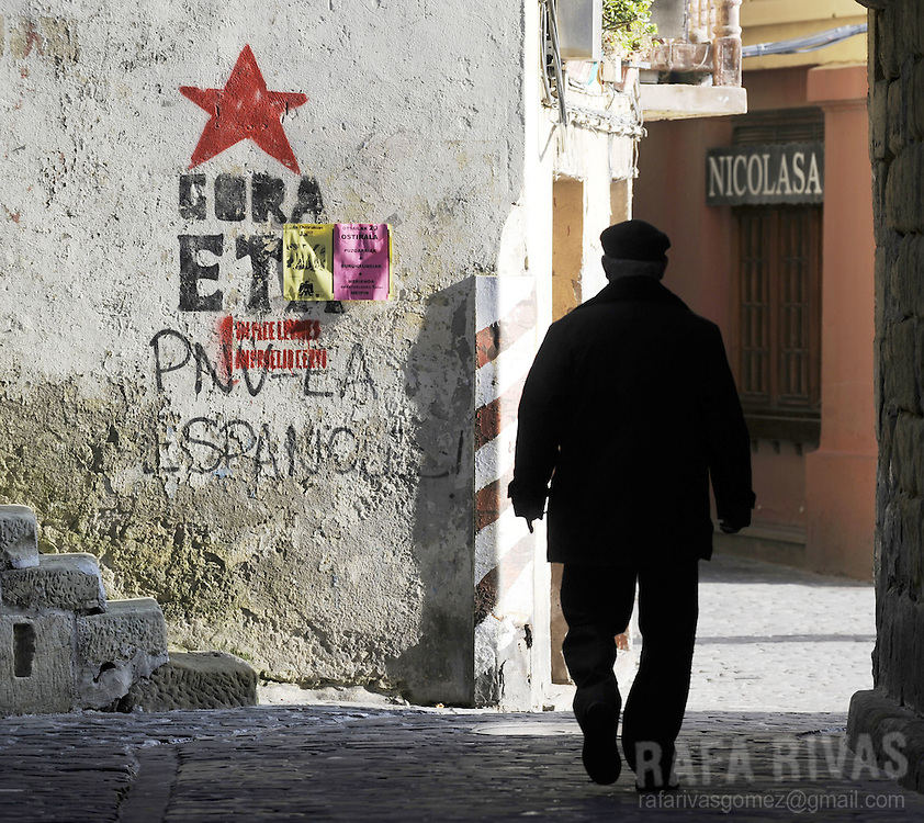 A man walks past graffiti in favour of armed Basque group ETA, in the northern Spanish Basque village of Pasajaes de San Pedro, on February 18, 2009.