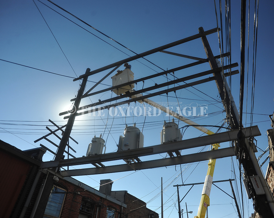 The Oxford Electric Department's Neil McCuiston and Scott Black remove overhead lines and transformers on South 11th behind the west side of the Square in Oxford, Miss. on Tuesday, October 23, 2012.
