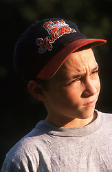 Portrait of young boy wearing baseball cap frowning,