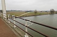 Nederland, Hedel, 20110309..De brug bij Hedel over de rivier de Maas. Er hangen repen stof aan de reling van de brug. De linten wapperen in de wind. Ter herinnering aan Joep Lennarts. .Sinds vrijdag 25 februari 2011 wordt fotograaf Joep Lennarts [53] uit Den Bosch vermist. Die dag is hij 's ochtends tussen 04.00 en 08.00 uur vanaf zijn huisadres vertrokken. Rond 08.30 uur hebben voorbijgangers zijn auto (een zilveren Opel Omega) zien staan op het fietspad bij de Hedelse brug nabij Café Treurenburg.  Sindsdien ontbreekt elk spoor van Joep...Netherlands, Hedel, 20110309.The bridge at Hedel over the river Maas. Strips of cloth hang on the railing of the bridge. The ribbons fluttering in the wind. In memory of Joep Lennarts. Photographer missing since Februari, 25th 2011