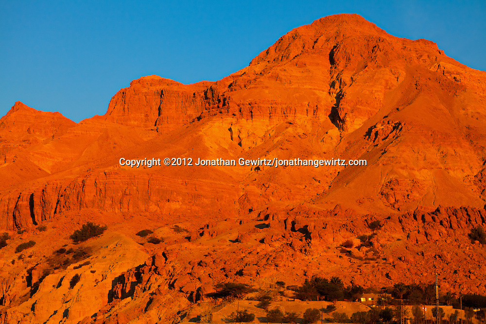 Warm sunlight illuminates the rocky hills near the Dead Sea oasis of Ein Gedi at dawn. WATERMARKS WILL NOT APPEAR ON PRINTS OR LICENSED IMAGES.