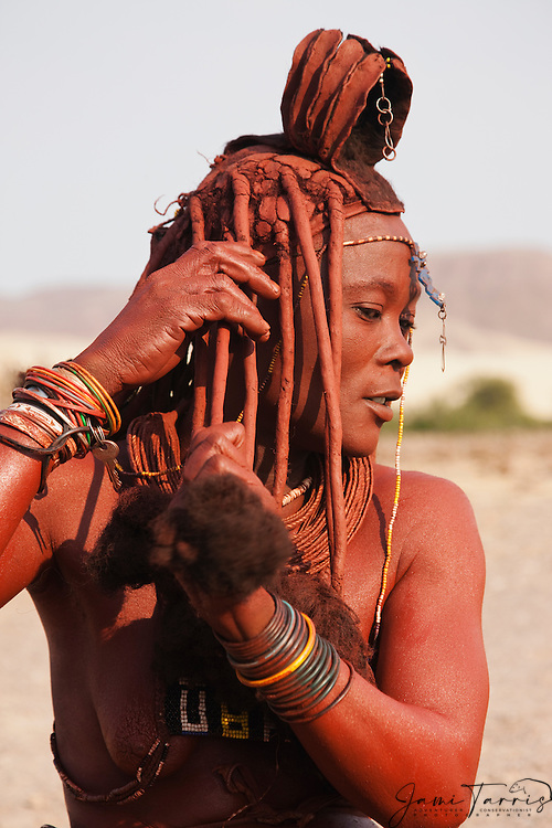 A Himba woman applying a fat and ochre mixture called otjize to her traditional hair,  Kaokoland,  Namibia,Africa