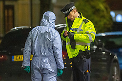 © Licensed to London News Pictures. 16/02/2020. London, UK. A forensic investigator talks to a uniformed police office at the scene of a multiple stabbing in Barking. Photo credit: Peter Manning/LNP