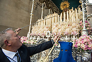 Men work incessantly to keep the hundreds of candles on the float carrying the Virgin Mary, burning. Granada, Andalusia. Spain