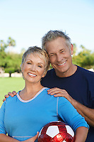 Senior couple holding soccer ball in park, portrait