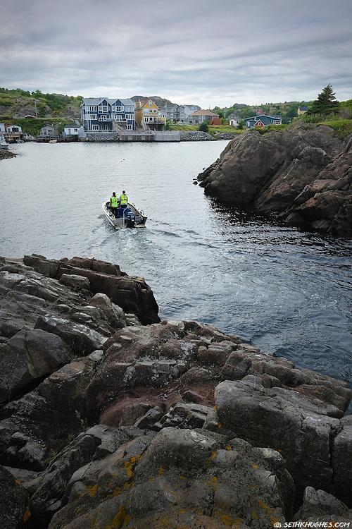 A fishing boat cruises into Quidi Vidi Harbor, St. John's, Newfoundland, Canada.