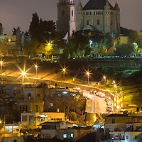 Israel, Jerusalem, Tomb of David and Dormition Abbey near Zion Gate along old Walled City on winter night, viewed from Mount of Olives