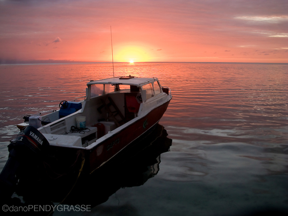 A boat is lit by the dying light of the warm Caribbean sun. Roatan, Honduras.