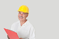 Portrait of happy senior constructor with clipboard over gray background