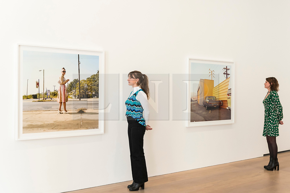 """© Licensed to London News Pictures. 10/04/2019. LONDON, UK. Staff members view works by American photographer William Eggleston at his new exhibition """"2¼"""" at the David Zwirner gallery in Mayfair.  The show comprises a series of square-format colour photographs taken around 1977 throughout California and the American South and will run April 12 to June 1, 2019. Photo credit: Stephen Chung/LNP"""